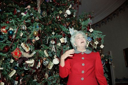 First lady Barbara Bush shows off the White House Christmas tree in the Blue Room, Monday Dec. 12, 1989, in Washington. The first lady was conducting a tour for members of the press. (AP Photo/Dennis Cook)